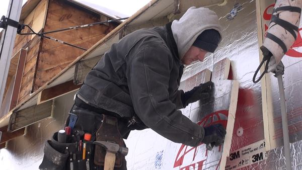 Mitchell trims the edge of the insulation sheet with a knife. Corners and eaves create challenging and laborious detail work on this project.