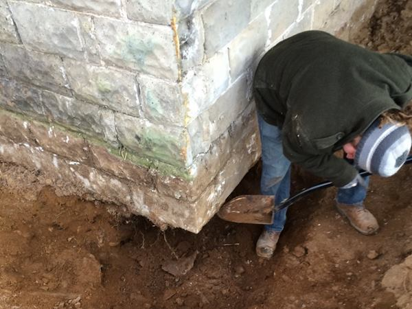 Mason Joe Martignetti hand-digs under the corner of the block foundation wall to start the underpinning work.