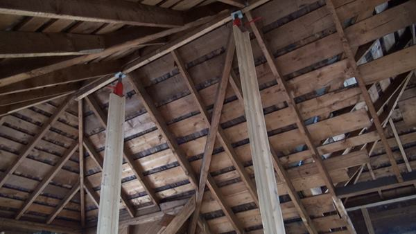 In the upper story, long temporary strongback posts topped with bottle jacks were used to lift the ridge of the complex hip roof, while comealongs were used to draw in the kneewalls of the house, which had splayed outward over the years.