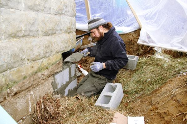 Portland mason Joe Martignetti repairs the building's block foundation last winter. The existing foundation wall remained porous to air and moisture after the patching and repointing, but the crew applied rigid foil-faced polyiso to the interior to control heat, air, and moisture flow.