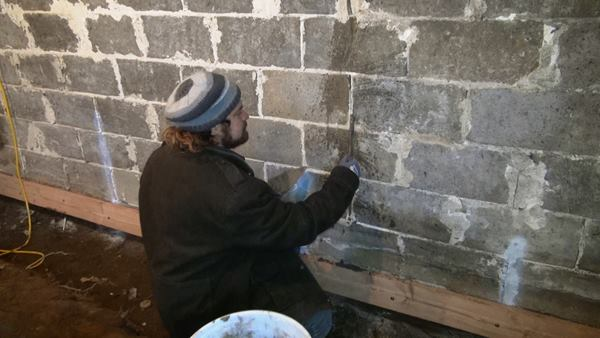Joe Martignetti repoints the interior of the basement wall in early winter of 2014. This wall face later received a cementitious parge, but remained vapor and air permeable.