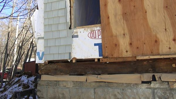 A view of the juncture between the existing foundation and wood frame, showing the existing siding, Tyvek housewrap, and sawn wood sill timber. The crew has already jacked up the sill a few inches in this view, in order to apply a Grace bituminous and polyethylene seal sealer.