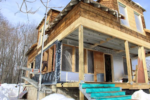 A view of the house during building envelope renovation in mid-winter shows the wall treatment in cutaway view. Existing rough board sheathing and rafter tails are seen at the top of the photo. In the near corner, all the layers of the exterior wall assembly can be seen: first, a layer of Grace Ice and Water Shield, tied into the flap of membrane already inserted between foundation and sill beam; then, successive layers of 1.5-inch foil-faced insulation. Later, the foam will be strapped for a vented rain-screen clapboard siding system.