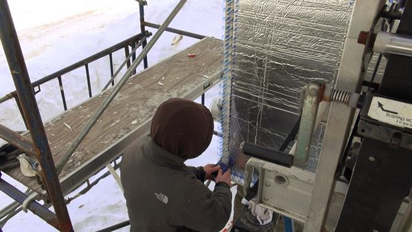 A worker applies Dow Weathermate tape to the inner layer of rigid foil-faced foam.