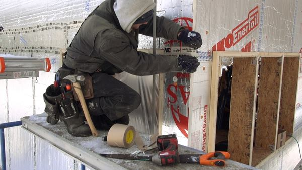 A carpenter applies 3M 8067 tape to the outer drainage-plane layer of rigid foam insulation. The crew accomplished the wall build-out during the severe winter of 2014 despite bitter cold and snow depths of 5 or 6 feet.