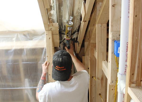 "An ""Itchy and Scratchy"" worker uses gun foam to seal and insulate small gaps in the wall and rafter framing."