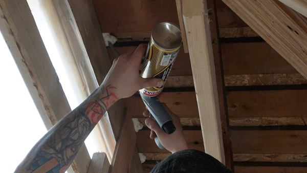 An insulating crew member squirts gun foam into gaps between the existing roof's skip sheathing.