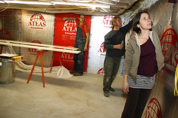 Crew members Will Markow and Dale Cunningham and architect Rachel Conly feel for air leaks at the top of the basement wall's interior rigid insulation layer. Air intrusion at the top of this wall was noticeable during the blower door test.