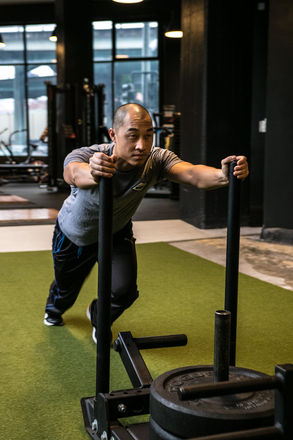 DIAKADI Trainer Derrick Lee push sled turf.jpg