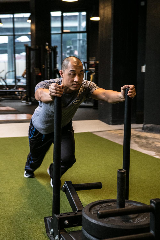 DIAKADI Trainer Derrick Lee push sled turf.jpg