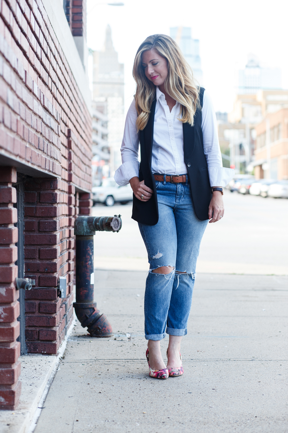 White button down black vest with boyfriend jeans and floral pumps for fall transition on Sophisticaited.com