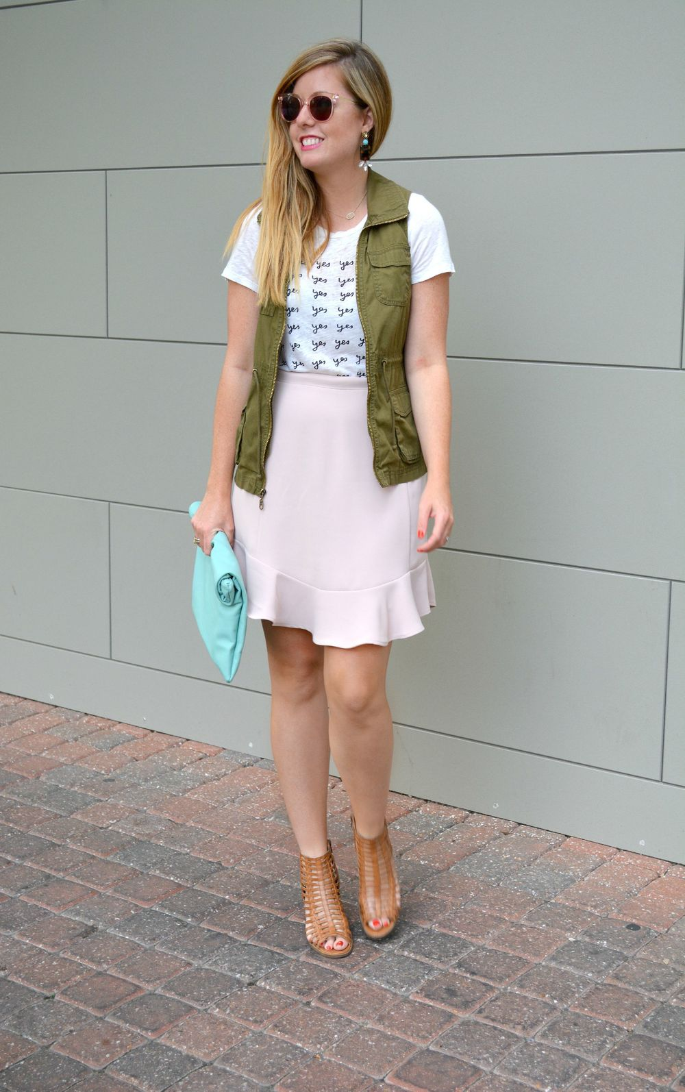 Graphic tee with cargo vest and pink skirt with mint clutch and brown cage sandals on Sophisticaited.com