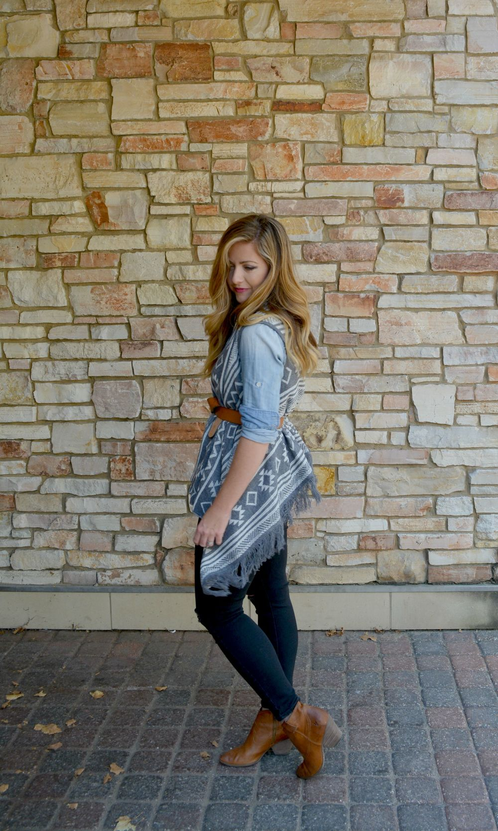 Aztec gray and white vest with chambray shirt black distressed jeans and cognac booties and belt on Sophisticaited.com