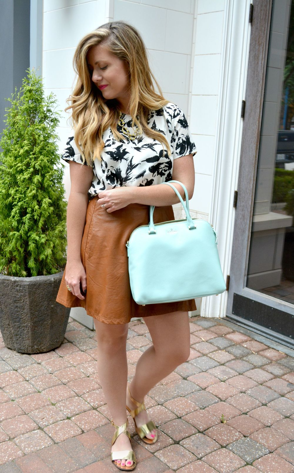 Black and white printed top with brown leather skirt mint Kate Spade bag with gold sandals on Sophisticaited.com