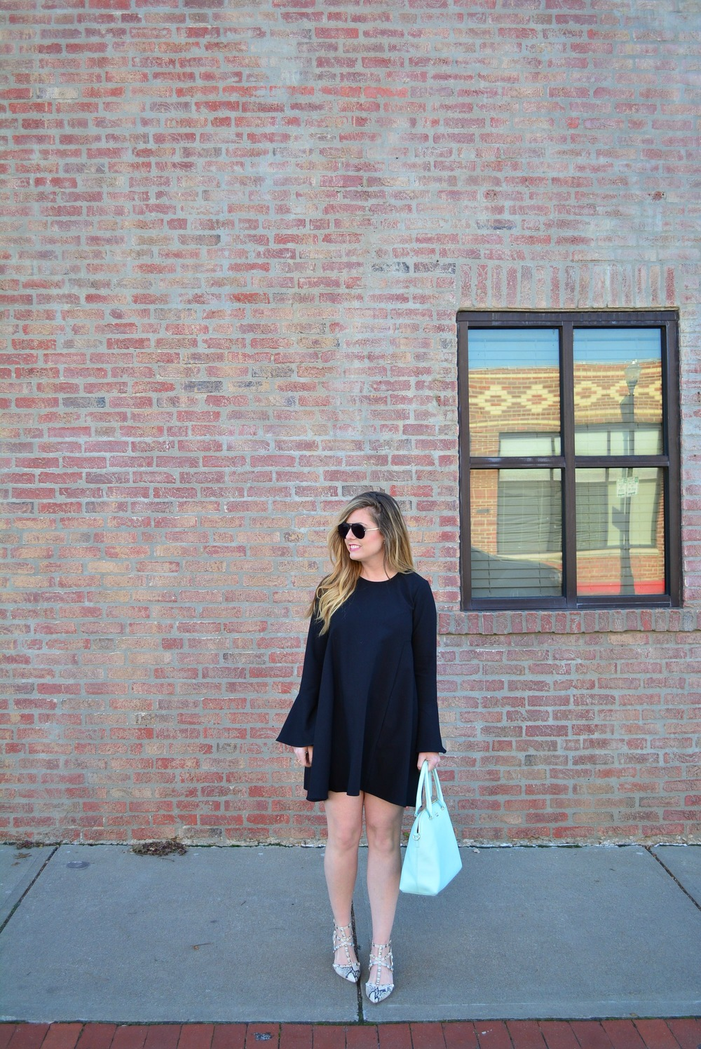 Black bell sleeve dress with snakeskin pumps and Kate Spade bag