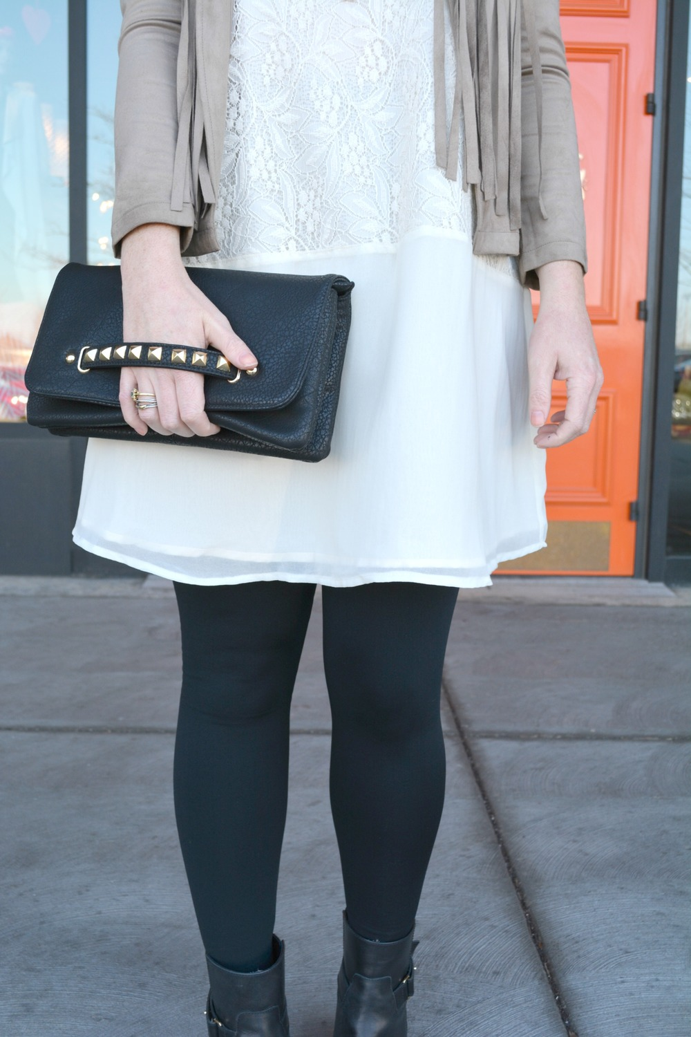 Black studded clutch with white lace dress and suede fringe jacket for spring
