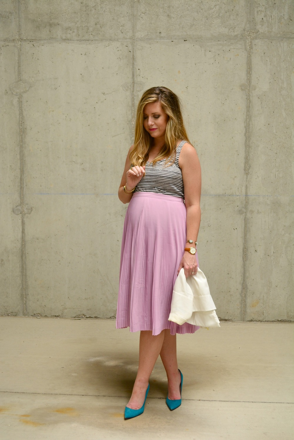 Dressy maternity outfit with a white drapey vest, stripe tank, and pleated pink J.Crew skirt