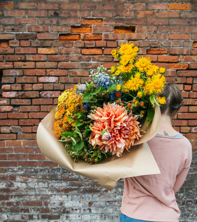 holding+flowers+by+brick+wall.jpg