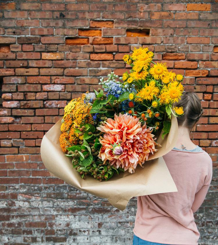 holding+flowers+by+brick+wall.jpg