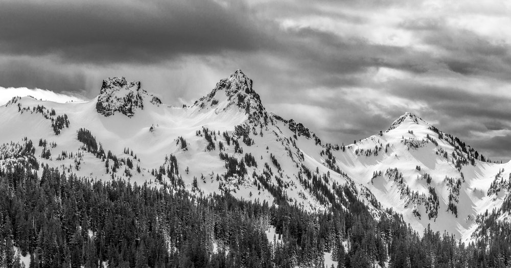 A brief moment of sunshine illuminates the Tatoosh Range during a snowstorm, Mount Rainier National Park, WA