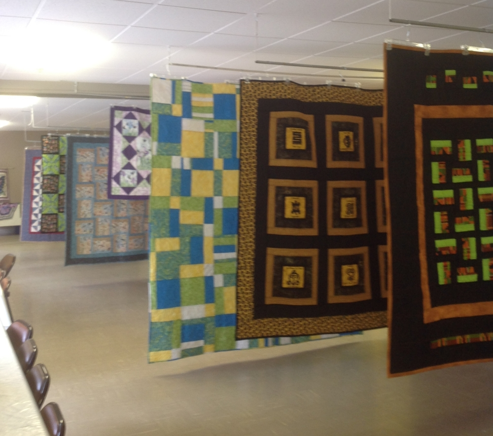 Quilts were hung from the ceiling in many rows.