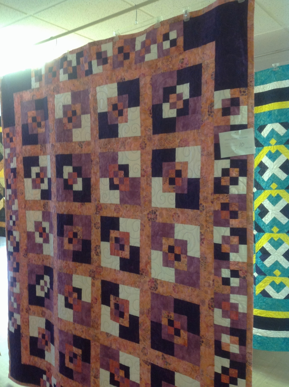 A beautiful example of quilt made from contrasting fabrics in purples and oranges.