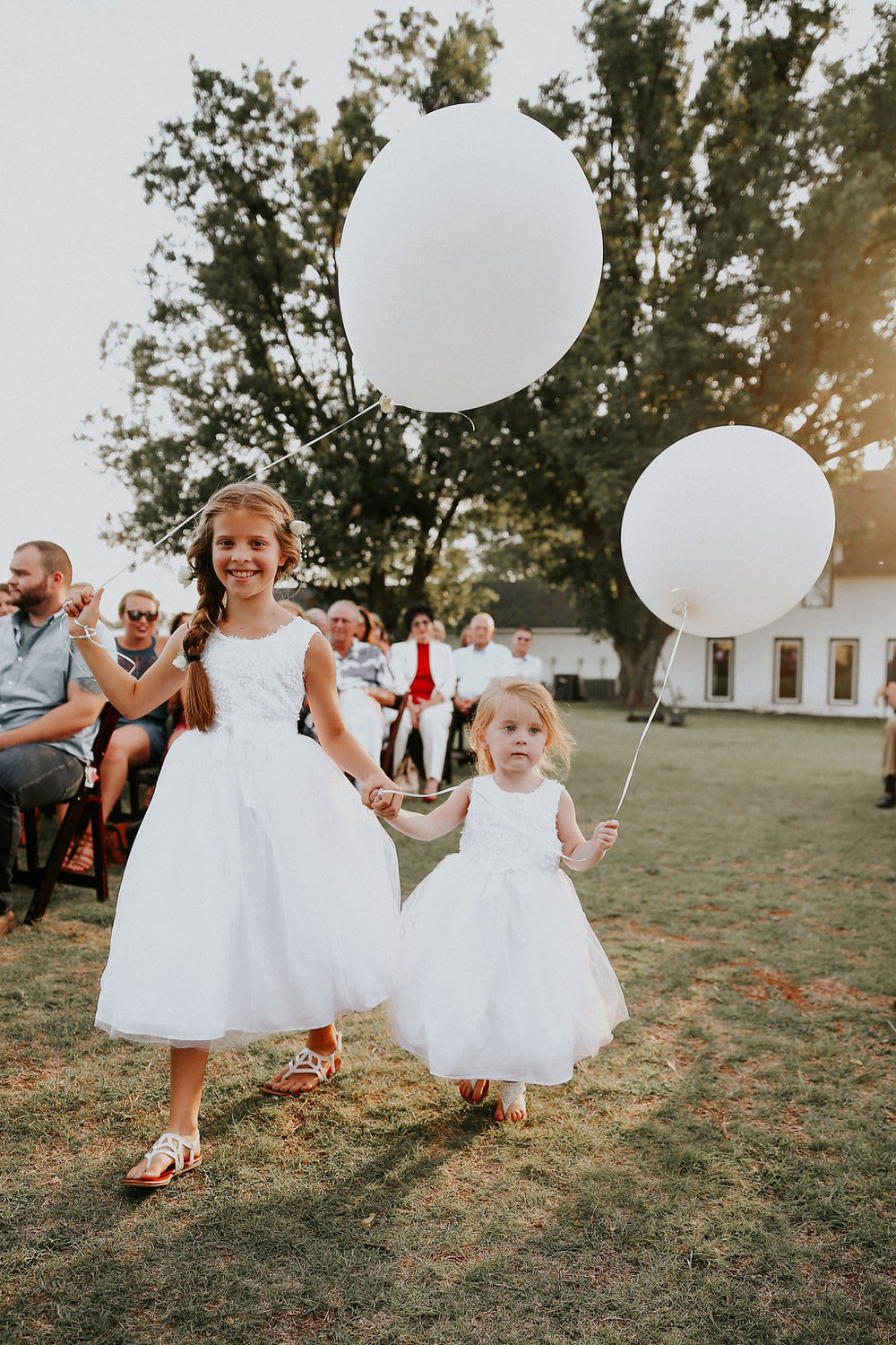 The sweetest girls lead the way down the aisle with giant balloons in tow
