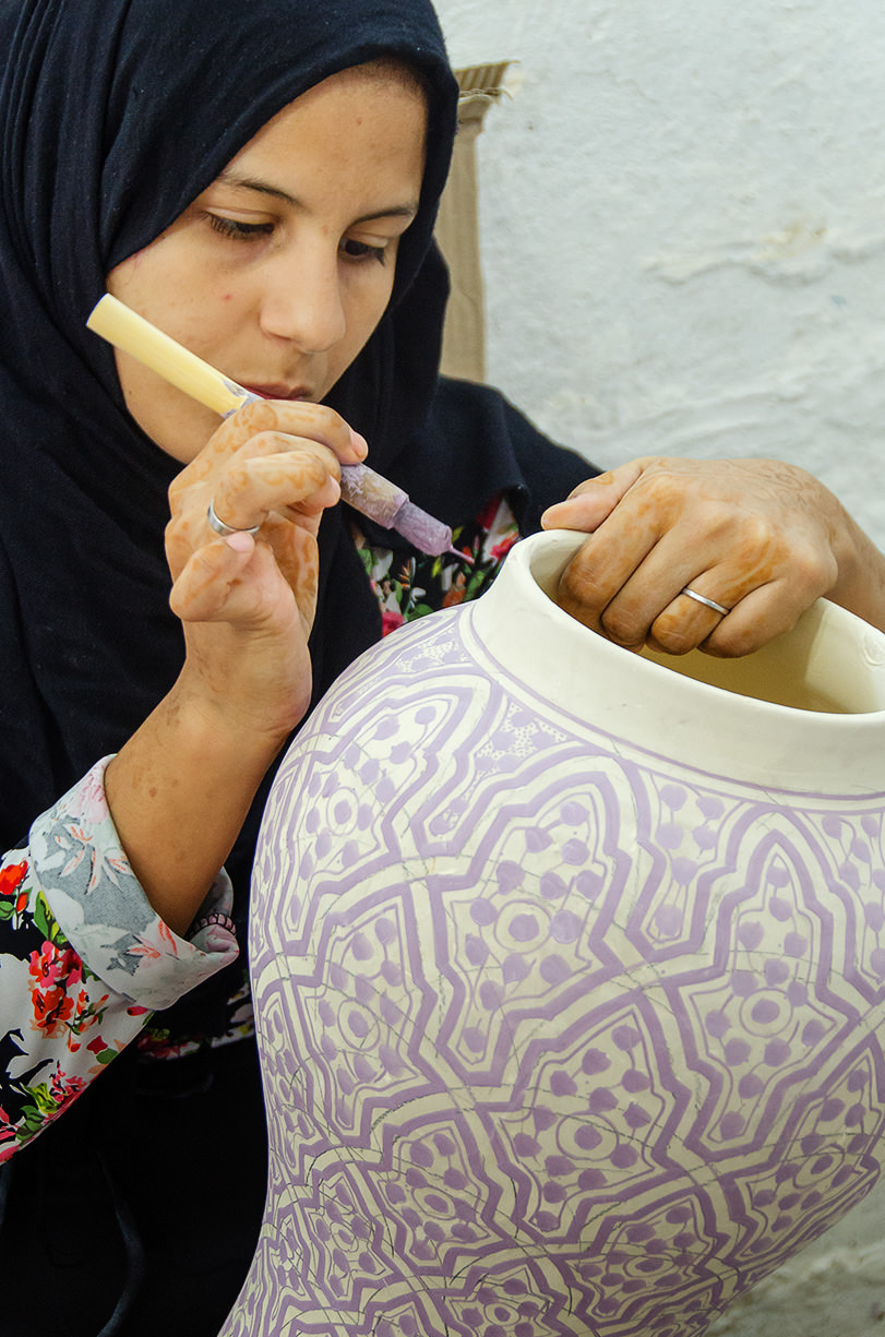 An artist decorates a vase with glaze at a potters' cooperative, Fes, Morocco