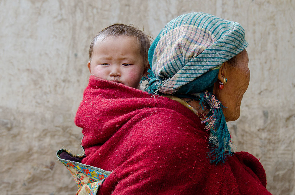In a rural village, a woman carries a young child