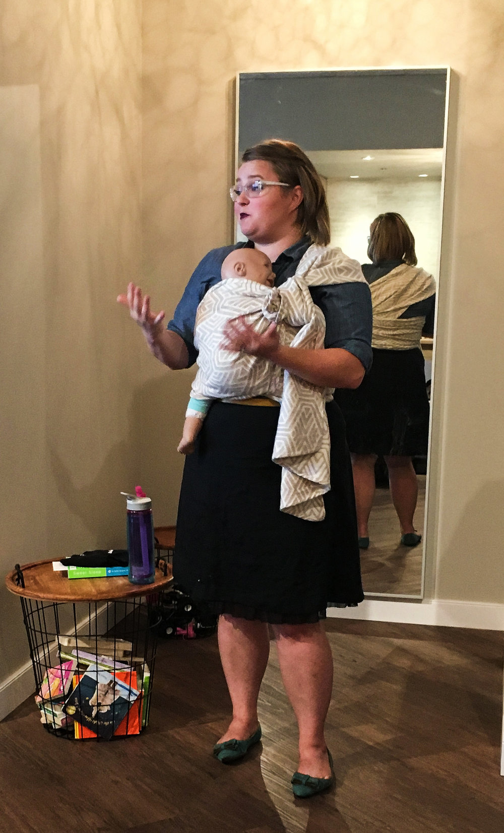 Photo by Shoena Strudwick of Yo Mama Maternity [Image description: A white woman with shoulder-length brown hair wearing glasses stands with her back to a full-length mirror. She is wearing a black skirt and has a baby wrapped on her front in a pale wrap.]
