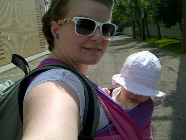 On our way to return books at the library and pick up some more. [Image dscription: A white woman wearing sunglasses and earphones takes a selfie while wearing a backpack and a small baby on the front in a pink and purple wrap.]