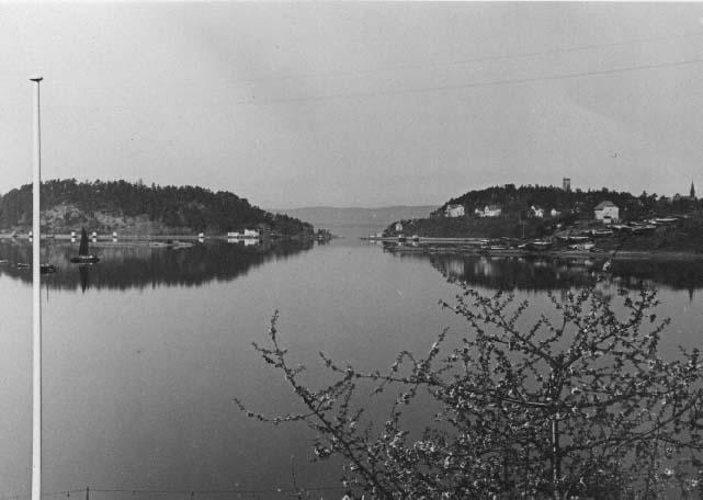 Malmøya og Ormøya (til høyre). Den nåværende broen over sundet kom i 1965. I høyre bildekant ser vi Ormøya kirke fra 1893. Øverst på Ormøya er det et et ca 20 meter høyt observasjonstårn av tre som tyskerne satte opp under krigen. Dette var et ledd flyvarslingssystemet mot allierte flyangrep. Tårnet ble revet i 1950. Foto 1950