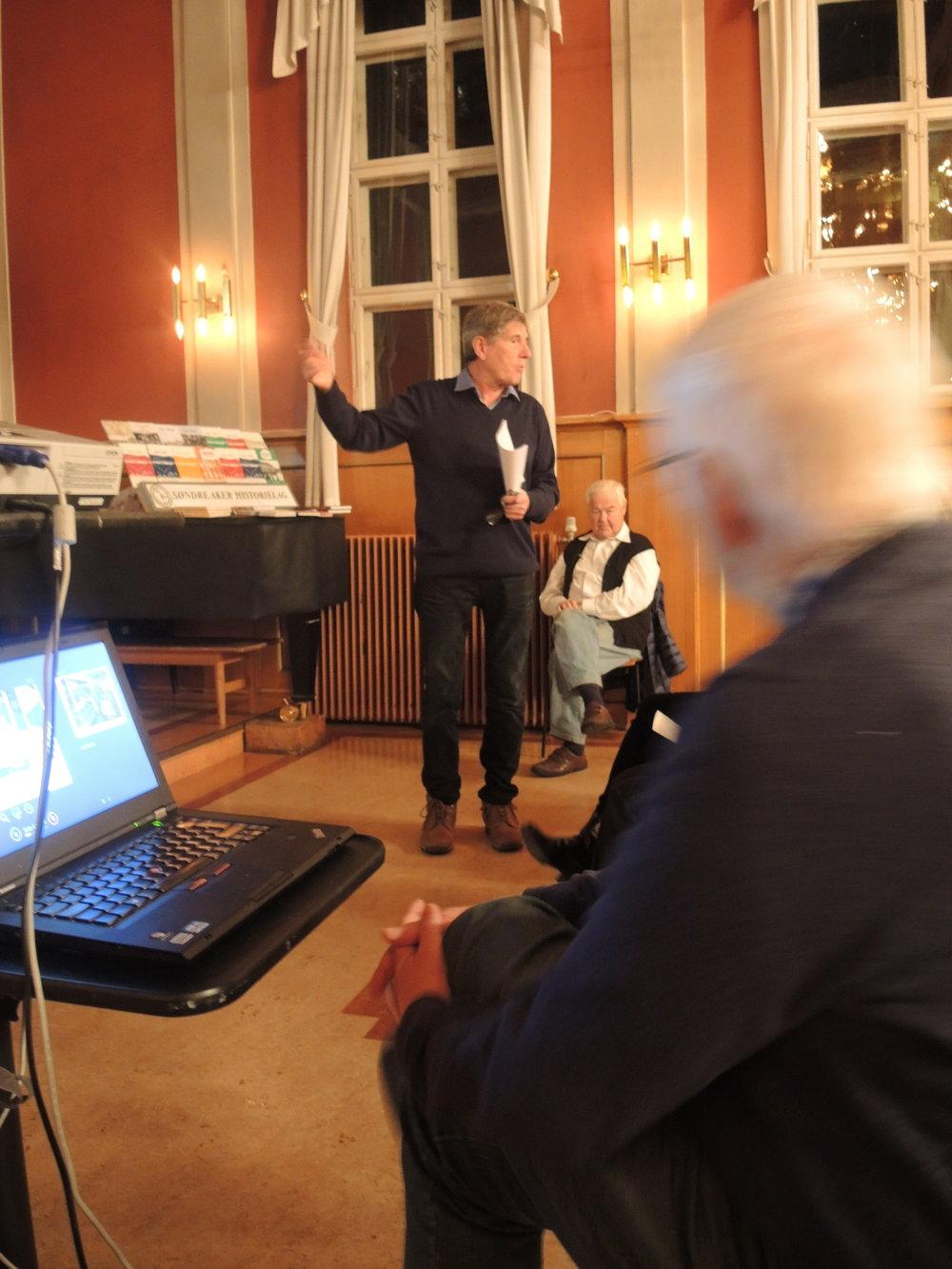 Prof. emeritus i økonomisk historie, Lars Thue, kåserte om veien fra mange tusen dagligvarebutikker til tre dagligvarekjeder. Her foran et bilde av familien Johansson, kaffegrossisten som i dag eier Norgesgruppen, som kontrollerer 41 prosent av dagligvarehandelen i Norge. (foto: Ivar Sekne)
