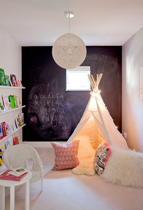 Make a decorative wall which at the same time is a creative corner, like this black board where they can draw new things all day long. The black boards ou can buy ready made or do it yourself by buying the special paint in stores. Create also a cozy corner for reading like this little Tipi, all children loves caves and small hiding places.