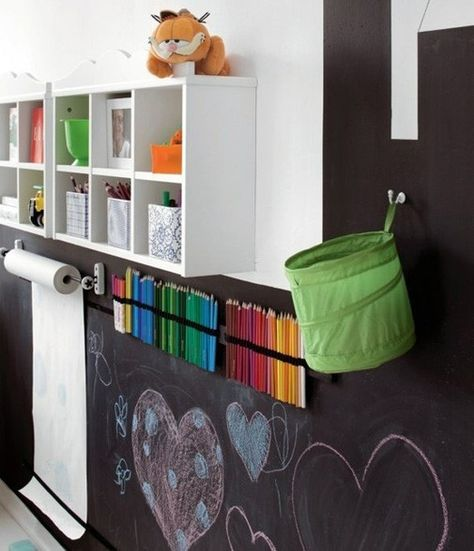 Fun, fun and pratical. Make a whole designer/leaning black board wall with pen holders, paper, containers for smaller things and shelfs. Attach black elastic with nails or glue to hold pens and use hooks for containers.