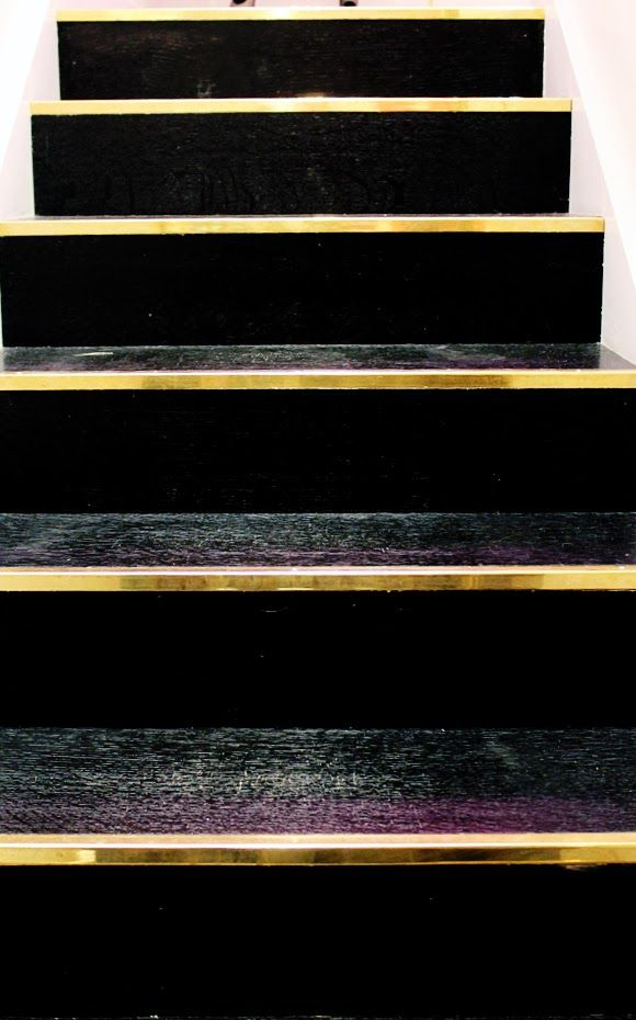 Staircase in black lacquer finished with gold metal strip. A very exclusive look.