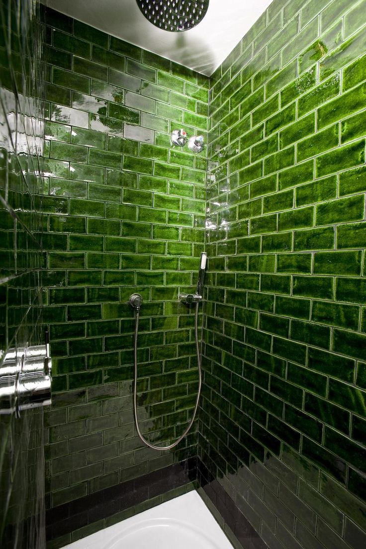 Dark green glazed tiles gives an amazing effect in a simple bathroom.