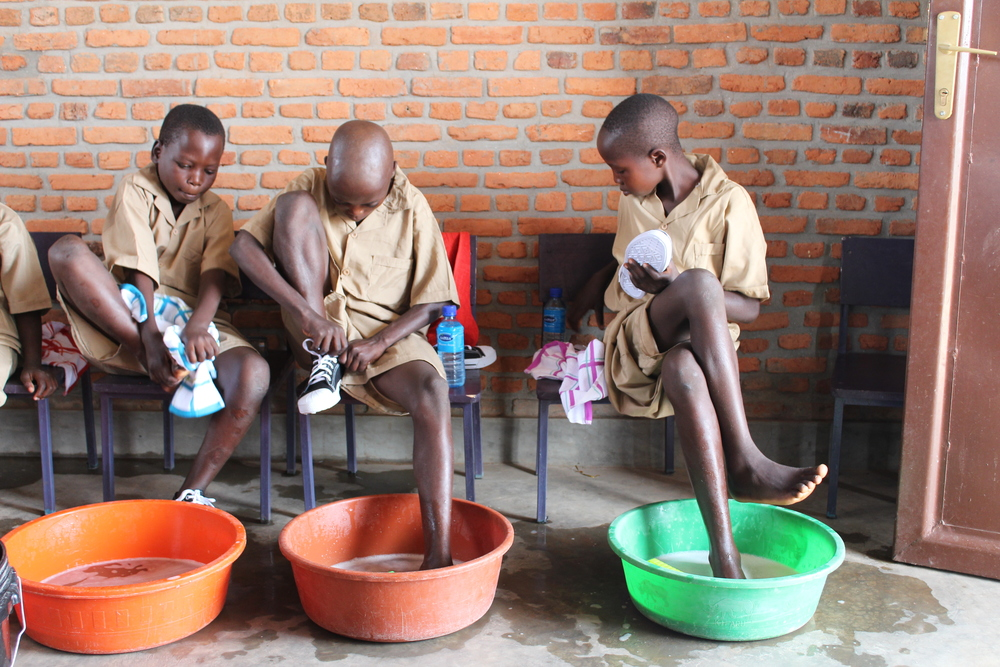 Students washing their feet before donning their new shoes.