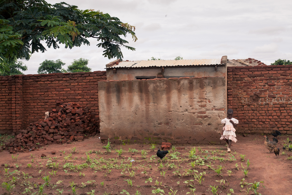 A girl comes from the latrine behind the school's vegetable plot.