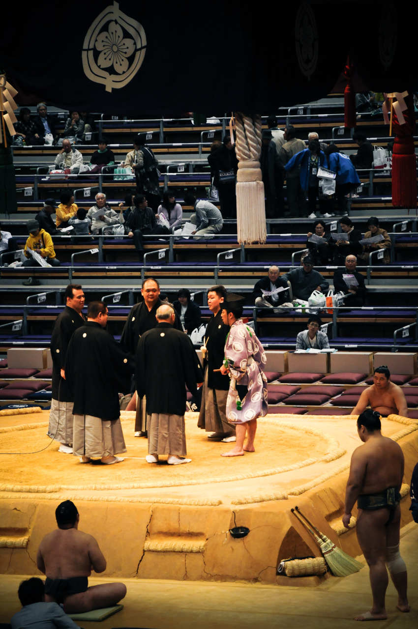 "The Sumo judges having a discussion about the referee's call.  These ""men in black"" have full say over anything during the matches."