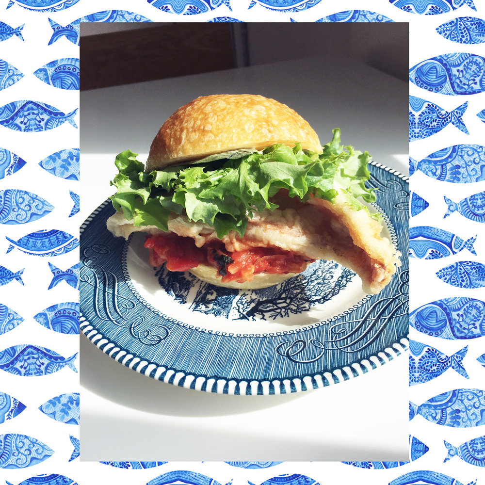 Fried Fish Sandwich w/ braised onion/tomato/garlic, basil & lemon caper mayo on a bun.