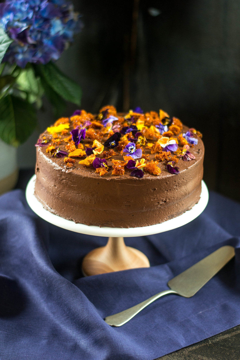 Honeycomb Chocolate Cake - What makes this gorgeous, rich chocolate cake so special? A bit of kitchen chemistry and the heart-shaped, scalloped leaves of edible viola flowers. Known as cinder toffee in England, fairy food in Wisconsin, yellow man in Ireland, and hokey pokey in New Zealand, honeycomb candy is an easy-to-make treat with interesting texture caused by carbon dioxide bubbles getting trapped when baking soda (sodium bicarbonate) is added to hot syrup. Violas begin popping up in early spring and add a charming and colorful bloom to the cake. Even chocolate lovers may be inclined to worry that this cake is just to pretty to cut. After the first crunchy, coffee nuanced bite of cake, however, it is hard to resist. Go ahead--dig in and have a second slice.