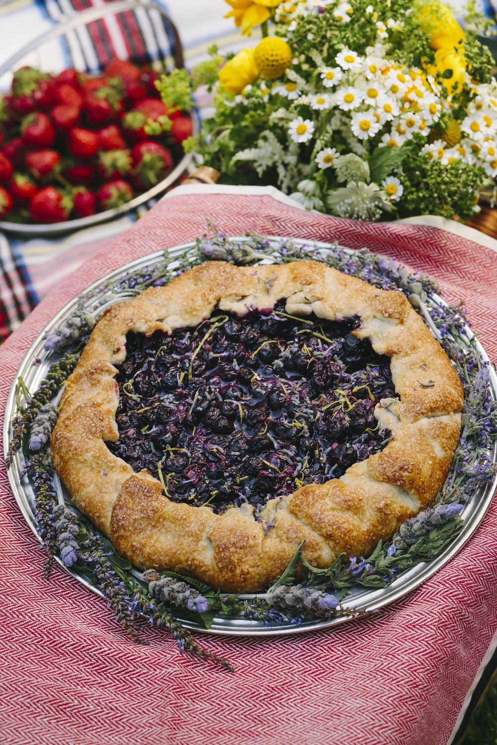 Rustic Blueberry, Lavender & Lemon Galette - In Montana, picking huckleberries in late August before the black, brown, and grizzly bears eat all was a right of passage--one in the bucket, two or three in the mouth. The mountainsides are purple with berries. Early in the season it does not matter how many are eaten, there are always plenty for making pancake syrup, huckleberry pie, and even leftovers for a few jars of jam for the pantry. Huckleberries, however, remain an uncultivated fruit and a grizzly bear's favorite dessert. What to do if this tiny berry is unavailable in New England? Blueberries of course! While bigger and lighter blue than their northwest cousins, blueberries are fabulous for baking whether fresh or frozen with the advantage of year round availability. Another perk? Picking without danger of ursus arctos horribilis lurking in the bush ready to swipe your filled pail and cause man versus beast pandemonium. Lavender, also harvested in late summer when blueberries are their berry best, compliments the sweet tangy taste of berries and looks gorgeous against the indigo blue of the fruit. When the galette is served with vanilla ice cream (highly recommended), the pie filling turns a lovely shade of Provençal lavender. A bit of lemon and this round wrapped fruit filled dessert, although rustic in appearance, has a sophisticated, complex taste capable of holding court at a formal dinner gathering.