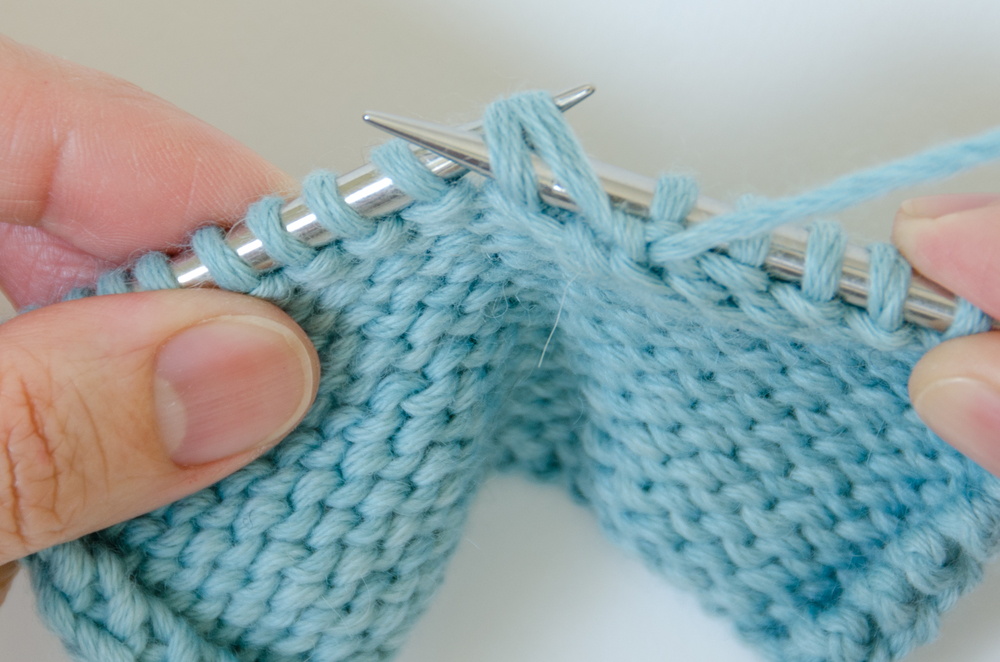 2. Place the wrap on the left needle and purl the wrap and the wrapped stitch together.