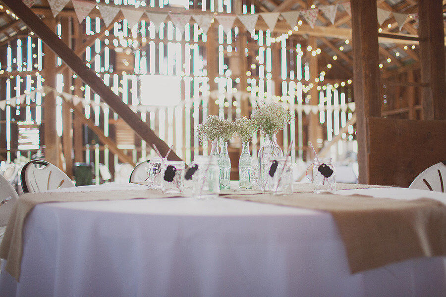 Copy of Vintage soda bottle vases and straws adorn the tables of this rustic wedding venue