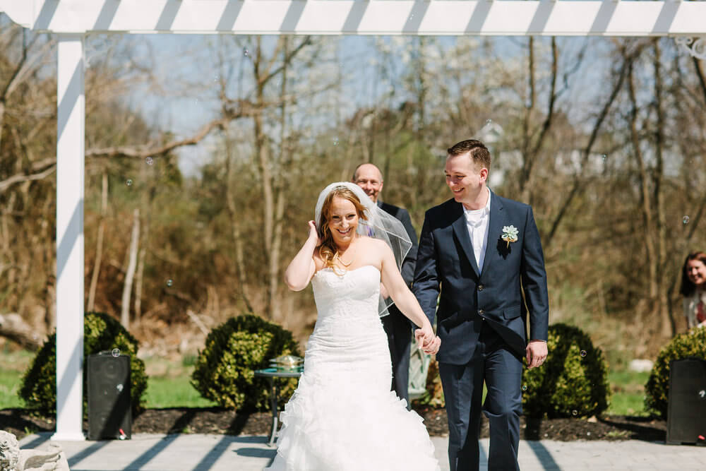 Copy of Bride and Groom walking down the aisle inside the wedding garden