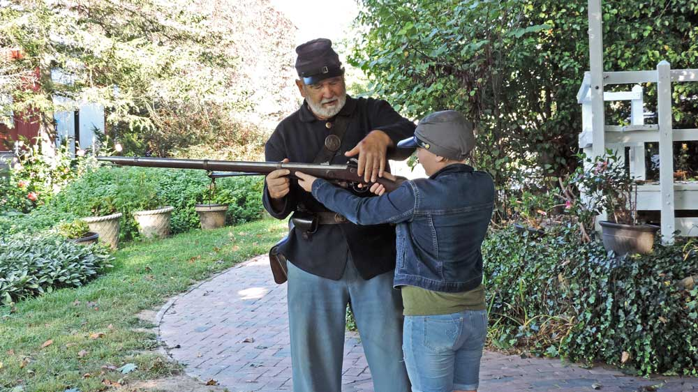 Mike Chambers instructing a young guest on how to fire a musket