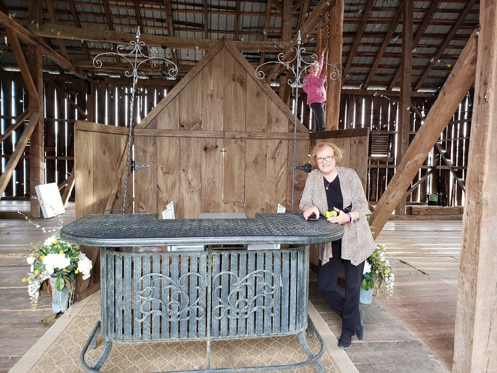 Debbie working on the wedding show booth in the barn while granddaughter Parker climbs behind her.