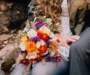My bouquet of white roses, zinnias, statice, euonymus, marigolds, cosmos, and assorted grass seedheads.    Photo by Taylor Heery: https://taylorheery.photography/