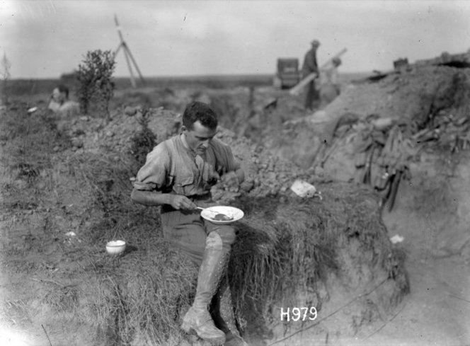 Bassett eating a meal in the trenches, 1917